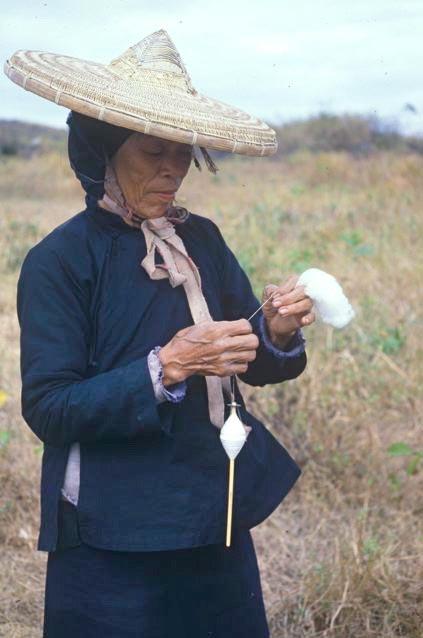 Mature Li woman drop-spinning kapok as she walks